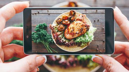 Kulinarisches Blog. Hobby kochen. Essen rezept. Nahaufnahme von weiblichen Händen, die gebratenes Fleisch mit gegrillten Pilzen fotografieren. Standard-Bild