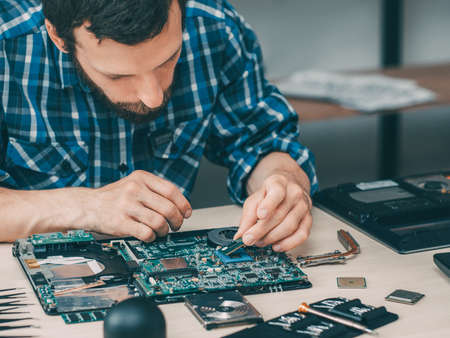 Computer technician workplace. Hardware repair upgrade. Man placing CPU on motherboard socket. Technology service. 스톡 콘텐츠