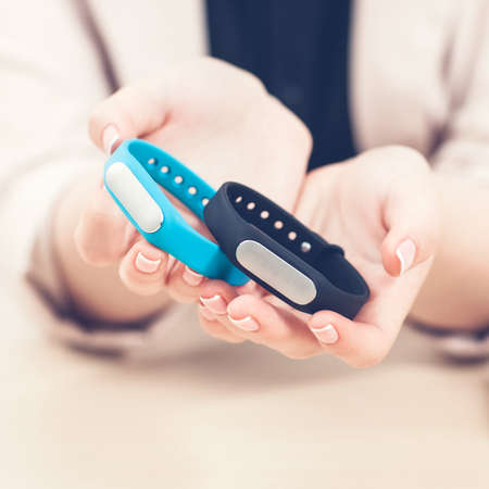 Fitness tracker presentation. Blue and black smart bracelets in woman hands closeup. Healthy lifestyle. Sport technology. Stock Photo