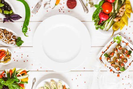 Food assortment top view. Empty white plate flat lay surrounded by dishes on the table. Buffet catering and restaurant cooking concept.