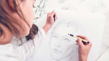 Hobby and leisure concept. Talent and creativity. Cropped shot of female artist drawing portrait on canvas. Stockfoto