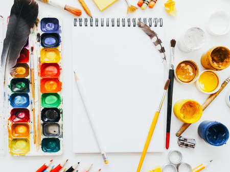 Creative artist workplace. Art workshop. Painting hobby. Flat lay of blank mockup sketchbook, pencils, paintbrushes and palettes.