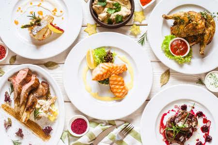 Draufsicht des Lebensmittelsortiments. Luxuriöses Buffet flach. Auswahl an Tellern und Speisen auf weißem Hintergrund Standard-Bild