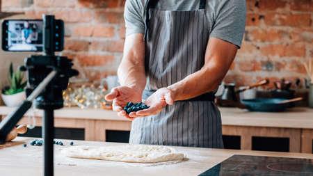 Influencer sui social. Food blogger che crea contenuti. Cuoco unico maschio che tiene i mirtilli, riprese video utilizzando la fotocamera su treppiede.