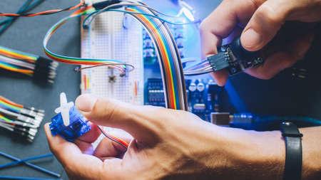 Ingeniero inventando prototipo. Construcción de módulo electrónico robótico. Programación de microcontroladores. Manos trabajando con sensor eléctrico.