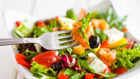 Healthy nutrition lifestyle. Closeup of rolled salmon slice on fork. Blurred vegetable salad background. Stock Photo