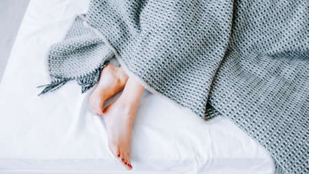 Home textile concept. Natural bed linen collection. Interior decor. Comfort rest. Woman feet peeking out from blanket. Stock Photo
