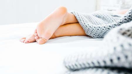 Voethygiëne concept. Behandeling en welzijn. Schoonheid en ontspanning. Close-up van vrouwelijke benen die uit de deken gluren. Stockfoto