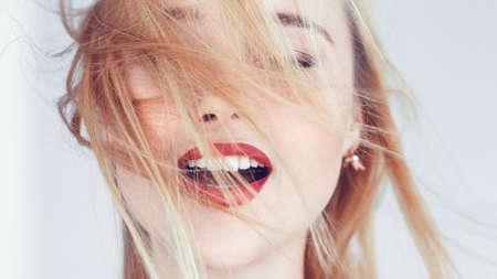 Portrait de jeune femme blonde. Cheveux au vent. Yeux fermés bouche ouverte. Émotions de relaxation de solitude de liberté.