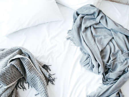 Morning awakening. New day beginning. Messy unmade bed. Cozy home textile in bedroom. Warmth and comfort.