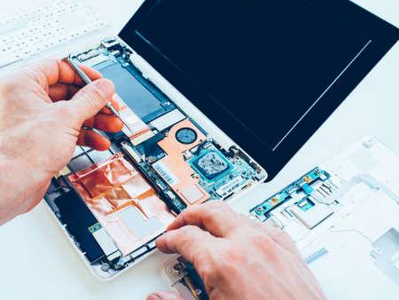 Servicio de reparación de portátiles. Actualización y mantenimiento de hardware de PC. Ingeniero arreglando cuaderno roto. Tecnologia computacional.