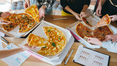 Millennials business lunch. Young team having break after successful work. Closeup of pizza in boxes on desk with charts.