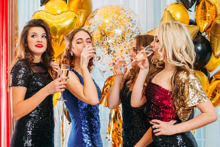 Fancy corporate party. Girls celebrating, drinking toast to company success in modern office decorated with golden balloons.
