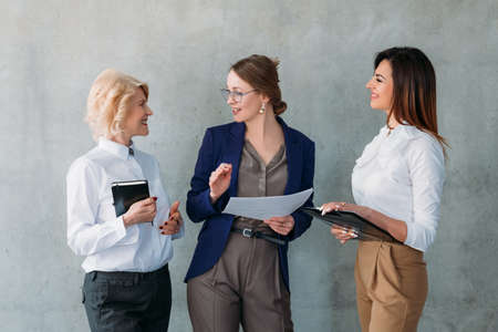 Conversation d'affaires. Femmes d'affaires matures et jeunes qui réussissent debout, discutant d'idées, plan stratégique. Banque d'images