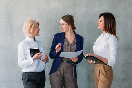 Zakelijk gesprek. Succesvolle volwassen en jonge zakenvrouwen staan, discussiëren over ideeën, strategisch plan. Stockfoto