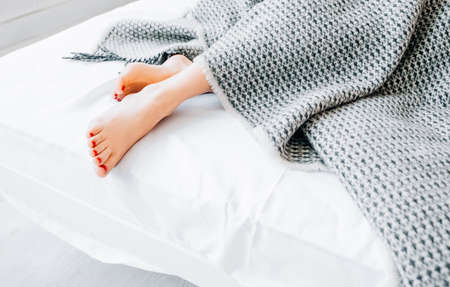 Home textile products. Natural bed linen collection. Interior design. Style and comfort. Woman feet peeking out from blanket. Stock Photo