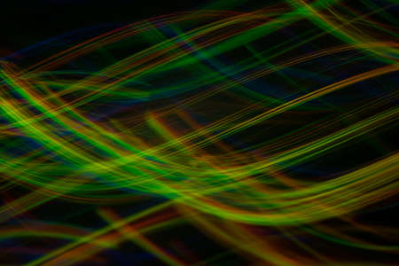 Blurred neon lights in motion. Thin curved multicolor lines on dark background. Lens flare effect.