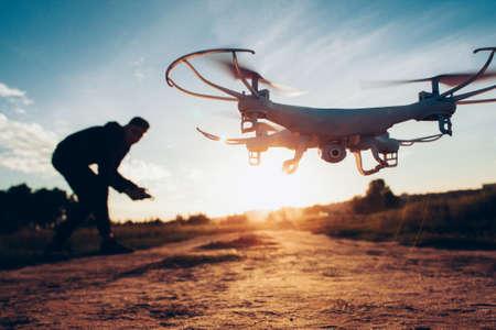 Drohnentrends und Innovationen. Modernes Hobby und Freizeit. Nahaufnahme des Kamera-Quadcopters, der von einem Mann über unscharfem Sonnenuntergang ferngesteuert wird. Standard-Bild