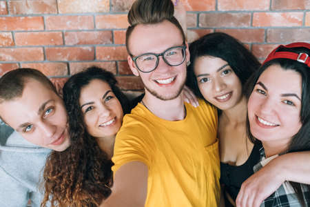Millennials relationship, firm friendship. Hipster guy taking group selfie with coworkers. Closeup of young cheerful people.