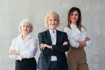 Successful business women. Professional career. Confident mature and young ladies standing with arms folded, smiling.