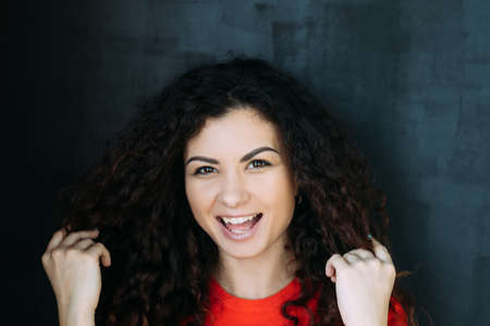 Closeup portrait of joyful smiling brunette lady with curly hair. Beautiful emotional young woman. Happy facial expression.