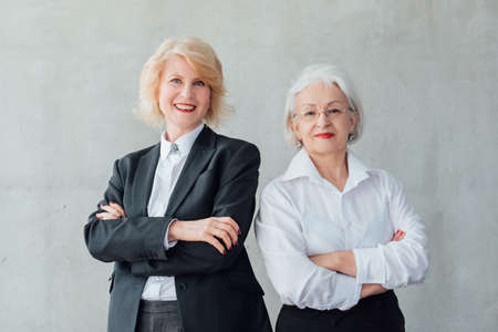Successful business women. Professional lifestyle. Strong female team. Confident mature ladies standing with arms folded.