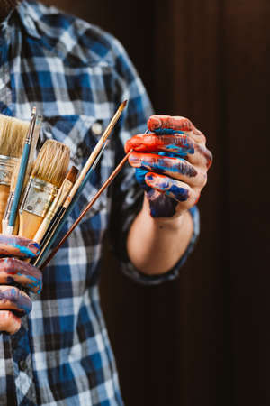 Art exhibition event. Painter master class. Cropped closeup of brushes in male hands dirty with paint. Man picking out one.