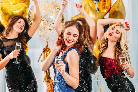 Fiesta elegante. Señoras celebrando su graduación universitaria en casa. Chicas bailando con champagne en habitación decorada con globos.