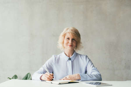 Succesful business career. Portrait of confident mature blonde woman sitting at desk with pen, notebook and tablet.