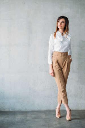 Femme d'affaires prospère. Jeune femme brune intelligente en tenue formelle debout avec les jambes croisées. Expression faciale réfléchie.