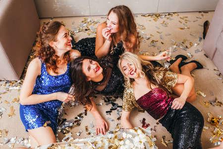 Celebración de fiestas de niñas. Ambiente relajado. Señoras divertidas con vestidos brillantes tirados en el suelo, divirtiéndose, riendo, confeti alrededor.