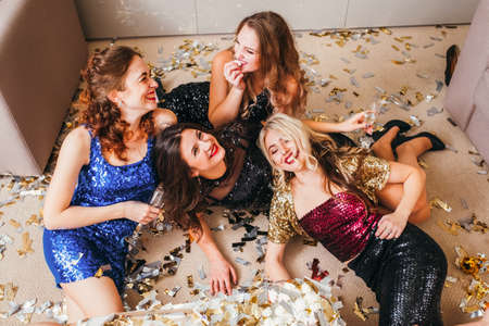 Mädchenparty feiern. Entspannte Atmosphäre. Amüsierte Damen in glänzenden Kleidern liegen auf dem Boden, haben Spaß, lachen, Konfetti herum.