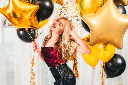 Birthday party. Blonde girl in dressy outfit dancing over white curtains with balloons. Pretty lady smiling with her eyes closed. Stock Photo