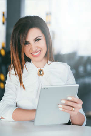 Business training. Successful female blogger. Information technology. Closeup portrait of young brunette lady sitting at desk with tablet.