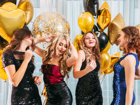 Girls party. Beautiful young ladies flaunting their festive looks and hairstyles, dancing over golden balloons. Stock Photo