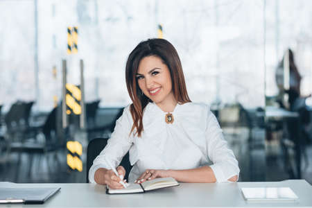 Successful female team leader. Young brunette business woman siting at desk with pen and notebook, smiling. 写真素材