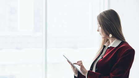Successful business lady. Corporate lifestyle. Side view of classy woman using tablet for work against big window. Stock Photo