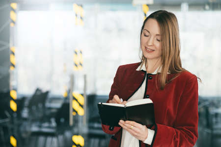 Corporate training. Successful professional career. Business woman standing at conference hall, taking notes, smiling.