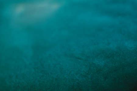 Abstrakter blaugrüner Farbhintergrund. Dunkler Cyan-Farbton. Unscharfes unscharfes Muster. Raue unebene Texturoberfläche. Standard-Bild