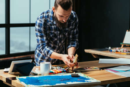 Artist at work. Studio atelier space. Bearded man painter with paintbrushes. Concentration inspiration focus on creative idea 스톡 콘텐츠