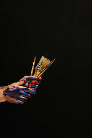Art class school courses. Man hands paint on holding bunch of paintbrushes. Basic supplies for artist style talent creativity.