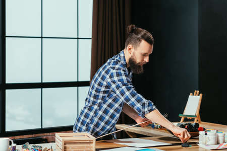 Artist workplace. Thoughtful bearded painter getting ready for creating artwork. Organizing tools gaining inspiration.