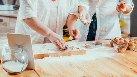 Women baking cutting flat dough making star shape cookies pastry. Sweet home bake foods goods. Cooking hobby leisure Stockfoto