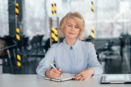Senior corporate ceo busy making notes in diary. Confident business woman planning meeting presentation consultation. Stock fotó