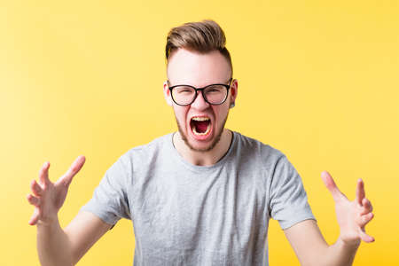 Portrait of fierce hipster guy on yellow background. Yelling young emotional man in glasses. Irritated facial expression. Copy space.