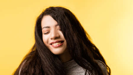 Portrait of happy, amused brunette girl with long strong hair. Sweet emotional lady with delighted facial expression, eyes closed.
