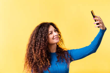 Selfie obsession. Social media addiction. Modern technology. Young lady using smartphone to take portrait photo. Empty space.