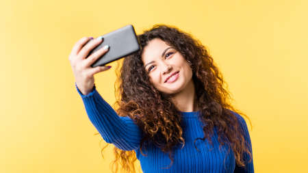 Narcissistic behavior. Social networking addiction. Young lady taking selfie on smartphone, smiling to camera. Empty space.