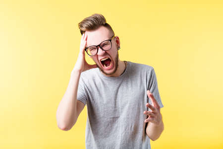 Portrait of stressed out hipster guy on yellow background. Frustrated, mad young emotional man shouting. Copy space.