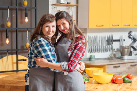 Happy women mother daughter hugging tightly. Close family bonding emotional connection. Good time together cooking.